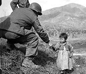Soldier helping Korean child